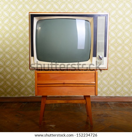 retro tv with wooden case in room with vintage wallper and parquet - stock photo