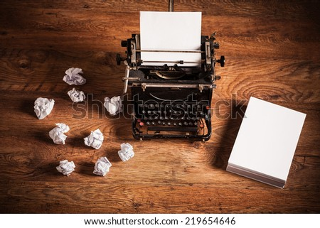 Retro typewriter on a wooden desk and a stack of paper beside it - stock photo