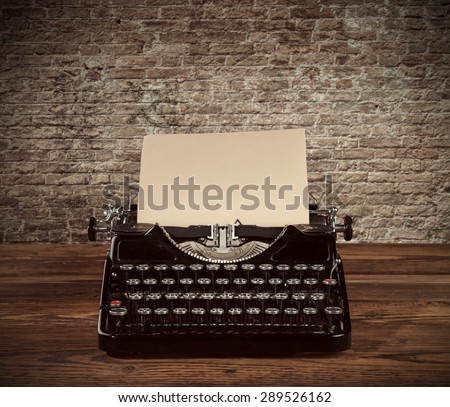 Retro typewriter placed on wooden planks. Old brick wall as background with copyspace. - stock photo