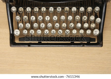 Retro typewriter with qwerty keyboard on a wooden desk - stock photo