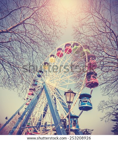 Retro vintage filtered picture of ferris wheel in a park. - stock photo