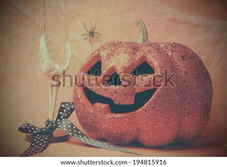 Retro vintage Happy Halloween party celebration jack o'lantern pumpkin and skeleton glass, cobwebs and spider on grunge style filter orange background. - stock photo