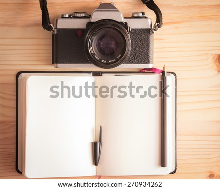 Retro vintage old photo camera with notebook and pen on a wooden table - stock photo