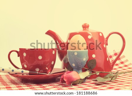 Retro vintage red check Happy Mothers Day or romantic Valentine breakfast with tea cup, tea pot and egg in red and blue polka dot 1950s style china. - stock photo