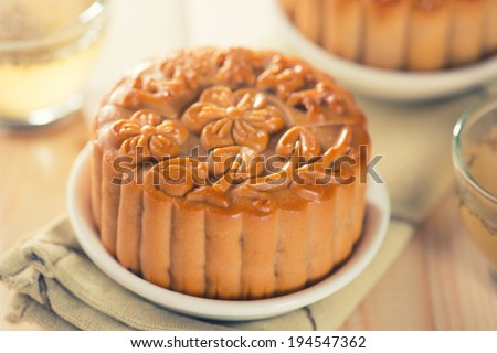 Retro vintage style Chinese mid autumn festival foods. The Chinese words on the mooncakes means assorted fruits nuts, not a logo or trademark. Traditional mooncakes on table setting with teacup.  - stock photo