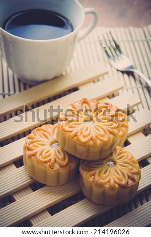 Retro vintage style Chinese mid autumn festival foods. The Chinese words on the mooncakes means assorted fruits nuts. Traditional mooncakes on table setting with coffee cup - stock photo
