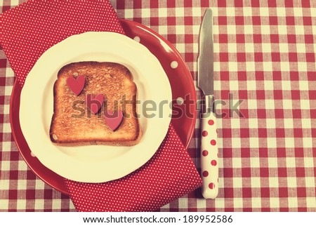 Retro vintage style red check table setting with polka dot plate and knife and toast with hearts for Mothers Day, romantic or Valentine breakfast. - stock photo