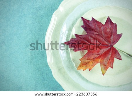 Retro vintage style Thanksgiving Fall dining table elegant place setting in pale aqua blue and white theme with autumn leaf, with copy space. - stock photo