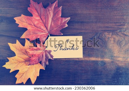 Retro Vintage style Thanksgiving table place setting with greeting tag and autumn fall leaves on rustic dark recycled wood background, with copy space. - stock photo