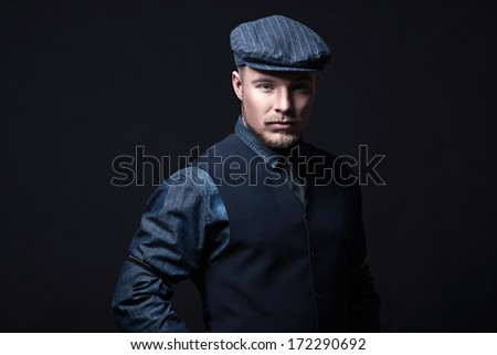 Retro winter fashion man. Wearing blue jeans shirt with gilet and cap. Blonde hair and beard. Studio shot against black. - stock photo