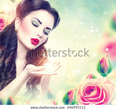Retro woman portrait in beauty pink roses garden. Beautiful Vintage styled girl with flowers blowing magic stars in her hand. Perfect makeup and hairstyle. Gorgeous model lady. Luxury Make up and Hair - stock photo