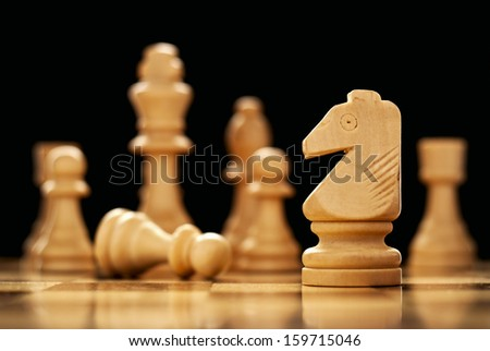 Retro wooden chess pieces on a chessboard with focus to a knight in the foreground, low angle view