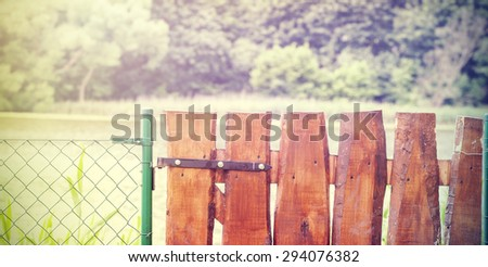 Retro wooden garden gate and wire fence. - stock photo