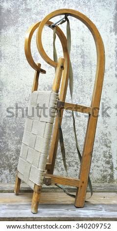 Retro wooden sledge on grunge background - stock photo