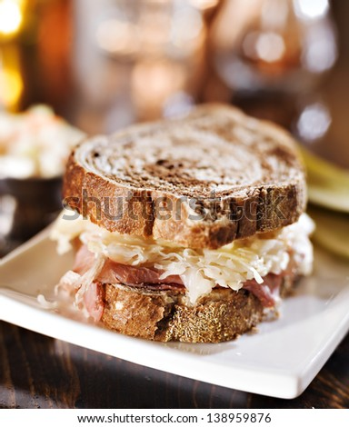 reuben sandwich with kosher dill pickle and coleslaw close up - stock photo