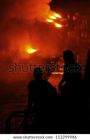 Revelers during the feast at St Julian in Malta engulfed in smoke tinged red from the flares they were lighting over water. - stock photo