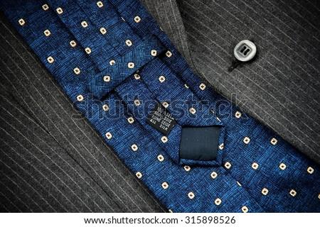 Reverse of blue silk tie with men's black suit. - stock photo