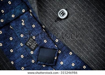 Reverse of blue silk tie with men's black woolen suit. - stock photo