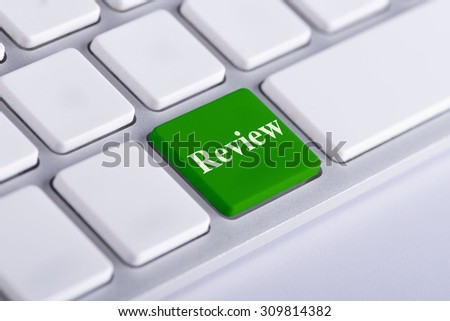 Review. Green word on keyboard, business concept