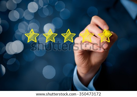 Review, increase rating or ranking, evaluation and classification concept. Businessman draw five yellow star to increase rating of his company. Bokeh in background. - stock photo