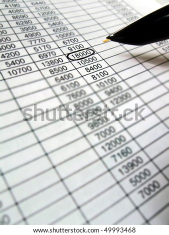reviewing the financial data spreadsheet with black ink pen. budget analysis concept - stock photo