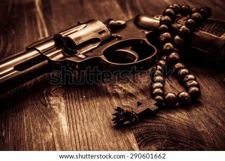Revolver and a rosary on the wooden table. Focus on the rosary. Close up view, image vignetting and the yellow-orange toning - stock photo
