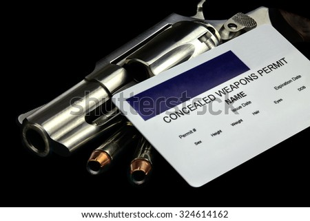 Revolver and Bullets and Concealed Weapon Permit. Selective focus and depth of field. - stock photo