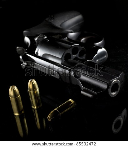 revolver and some cartridges on a black piece of glass - stock photo