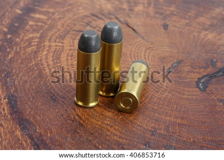 Revolver cartridges .45 Cal Wild West period on wooden background