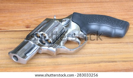 Revolver laying on wooden table - stock photo