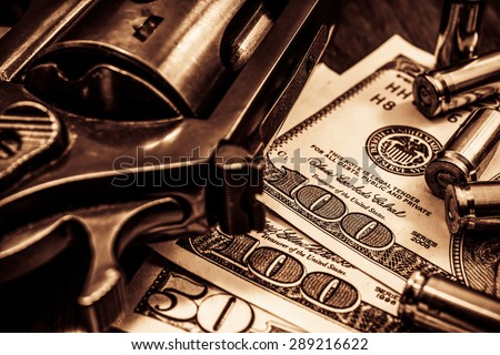 Revolver with cartridges and money on the wooden table. Close up view, image vignetting and the yellow-orange toning - stock photo