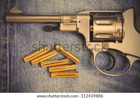 revolver with cartridges on old blue jeans background, close up. instagram image filter retro style - stock photo