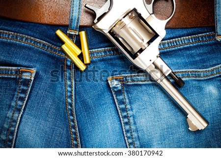 revolver with cartridges on old blue jeans with leather belt, close up - stock photo