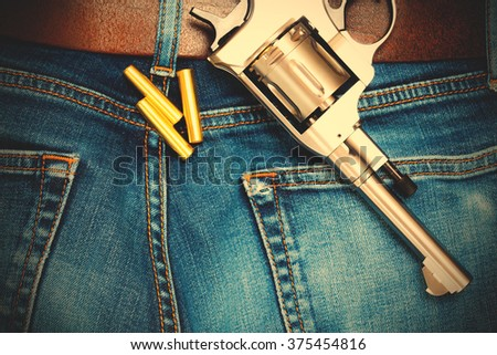revolver with cartridges on old blue jeans with leather belt, close up. Instagram image filter retro style - stock photo