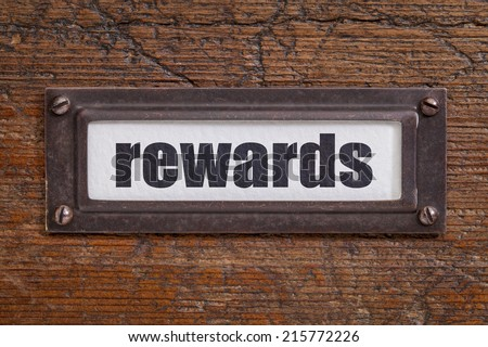 rewards - file cabinet label, bronze holder against grunge and scratched wood