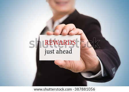Rewards just ahead message word on card in hand of Friendly man hand and smiling - stock photo