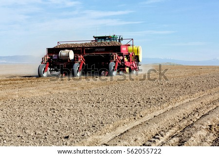 Rexburg, Idaho, USA May 3, 2016 A farmer using a tractor and planting implement, plants potatoes in the fertile farm fields of Idaho