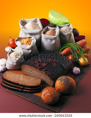 Rey bread loaf, muffins, grains and vegetables on orange background. - stock photo
