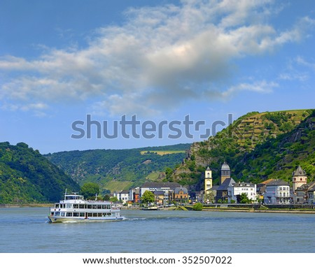 Rhine valley with cruise ship and village of Sankt Goarshausen, Germany. Rhine Valley is UNESCO World Heritage Site - stock photo