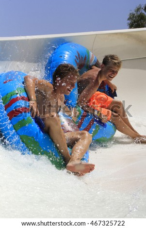 Rhodes, Greece-August 3,2016:Two boys on the rafting slide in the  Water park.Rafting slide is one of many popular game for adults and children in park. Water Park is located on the island of Rhodes