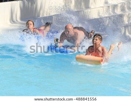Rhodes,Greece-September 3,2016:Family on the mat racer slide in Water park,Mat racer slide is very popular for young people in the Water Park. Water Park is located on the island of Rhodes