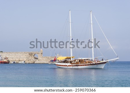 Rhodes, Greece - September 22, 2014: Sailing is a common activity of both, Greek and Turkish citizens that visit their common beautiful coastlines. Sailboat visiting the Greek island of Rhodes, Greece - stock photo