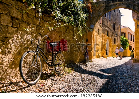 RHODES, GREECE - SEPTEMBER 30: Tourists admire charming secret narrow streets of Rhodes Island, bicycles in the foreground. September 30 2011, Greece - stock photo