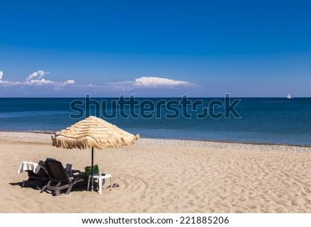 Rhodes Greece umbrellas on the beach - stock photo