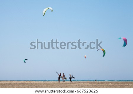 RHODES, PRASONISI, GREECE - APRIL 23, 2017 ; People practicing Kitesurfing. Beach on the peninsula Prasonisi, Rhodes. Colorful kites on the sea shore. Blue sea and windsurfing.