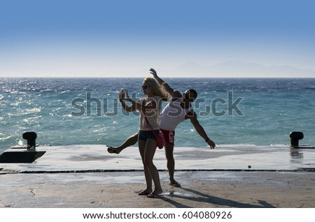 RHODOS, GREECE - JUNE 26, 2015: Aegean Sea and beautiful beaches of Greece Islands are popular recreatiin destination for around the world tourists. Pictured are unidentified tourists taking picture.