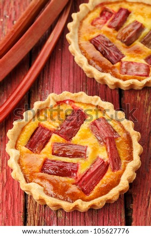 Rhubarb and saffron cream tart on a red wooden background