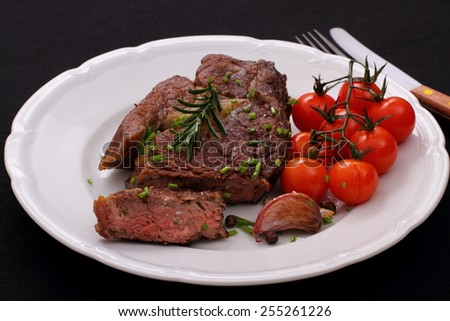 Rib eye steak, cherry tomatoes, garlic, herbs on black background - stock photo