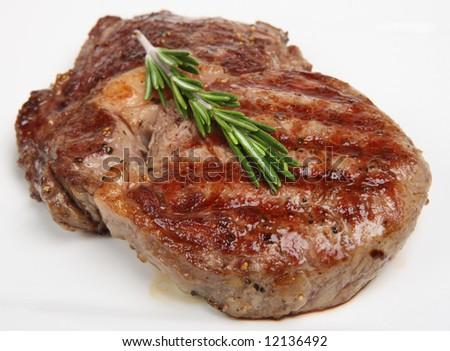 Rib-eye steak resting on a white plate - stock photo