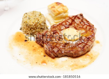 Rib eye steak with bulgur, butter and potato gratin, close-up - stock photo